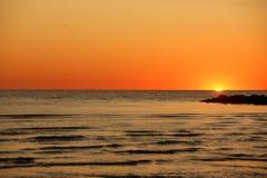 Solnedgång bak pir av stenar Royaltyfri Bild