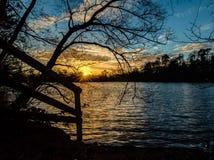 Solnedgång bak sjön Arkivfoto
