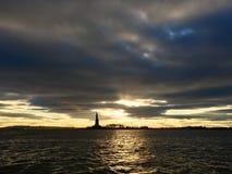Solnedgång bak statyn av frihet royaltyfri foto