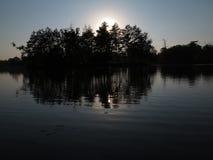 Solnedgång bak träd på ön arkivfoto