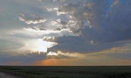 Solnedgång De ljusa färgerna av den molniga himlen och strålarna av solen Royaltyfria Foton
