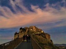 Solnedgång, färger, rosa himmel och moln, turister och saga i Civita di Bagnoregio, stad i landskapet av Viterbo, Italien arkivfoto