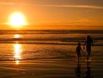 solnedgång för 2 strandsilhouettes Arkivfoto