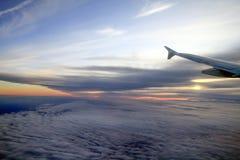 Solnedgång för hög höjd över molnen från ett plant fönster royaltyfria bilder