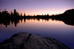 solnedgång för lakereflexionstoppig bergskedja Arkivfoto