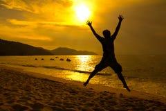solnedgång för strandbanhoppningman arkivfoto