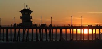 solnedgång för strandhuntington pir Arkivfoto