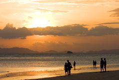 solnedgång för strandlookfolk till Royaltyfri Foto