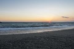 solnedgång för strandpebbleseascape stormigt hav Arkivfoto