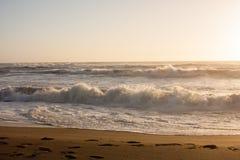 Solnedgång för strandvattenvågor Fotografering för Bildbyråer