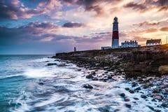 Solnedgång för Tid schackningsperiod på kust med fyren på klippor arkivfoto