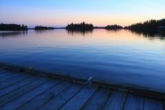 Solnedgång från fartygskeppsdockan, sjö av träna, Kenora, Ontario royaltyfri bild