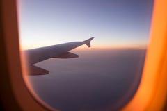 Solnedgång från flygplanfönster Arkivbilder