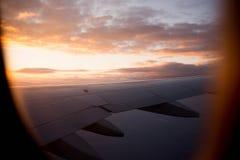 Solnedgång från flygplanfönster Arkivbild
