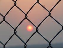 Solnedgång från stänger Arkivfoto