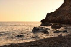 Solnedgång från stranden bak udden med orange färger royaltyfri bild