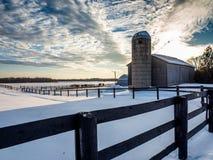 Solnedgång fryst lantgård för häst för staket för vintersnöstång Arkivfoto