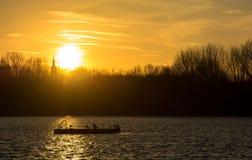 Solnedgång holländsk sjö och kyrka Royaltyfri Bild