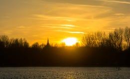 Solnedgång holländsk sjö och kyrka Arkivbild