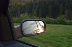 Solnedgång i backspegel Arkivbild