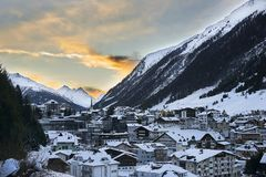 Solnedgång i berg Övervintra aftonen skidar in semesterorten Ischgl i Tyrol fjällängar Arkivbild