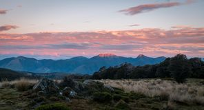 Solnedgång i bergen, Nelson Area, Nya Zeeland royaltyfria foton