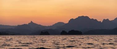 Solnedgång i bergen och havet royaltyfria bilder