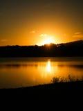 Solnedgång i Cassanges en sjö Arkivbild
