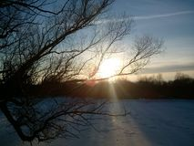 Solnedgång i den land fryste floden Arkivbild