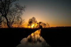 Solnedgång i en flod Arkivbild