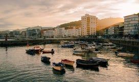 Solnedgång i en hamnstad, Castro Urdiales arkivbild