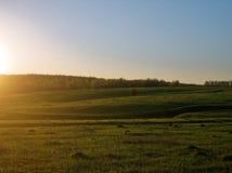 Solnedgång i ett fält på utkanten av byn Royaltyfria Foton