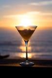 Solnedgång in i ett martini exponeringsglas Royaltyfri Foto