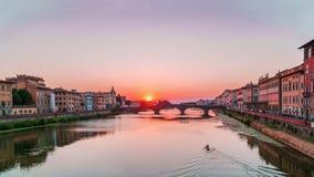 Solnedgång i Florence över den Arno floden och den ensamma kayakeren som ner går förbi floden Arkivfoto