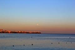 Solnedgång i havet med shorelinen i sikt Arkivfoto
