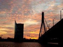 Solnedgång i himlarna ovanför stadsfloden arkivbild