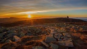 Solnedgång i jätteberg Arkivbild