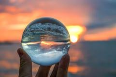Solnedgång i ljus apelsin med vågen som bryter på sand som fångas i den Glass bollen royaltyfria foton