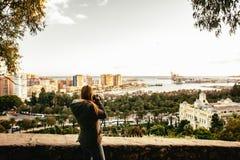 Solnedgång i Malaga, Spanien Kvinnafotograf som skjuter solnedgången på skeppsdockorna och den spanska staden Mediterrenean stad  arkivbild