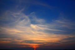 Solnedgång i moln mot den härliga aftonhimlen Arkivfoton