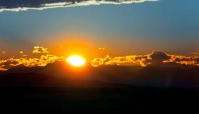 Solnedgång i molnen på bergen Arkivbild