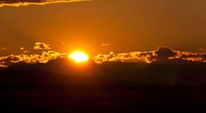 Solnedgång i molnen på bergen Arkivbilder