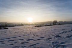 Solnedgång i purpurfärgat skimrande vinterlandskap med snö, Amstetten, Tyskland royaltyfri bild