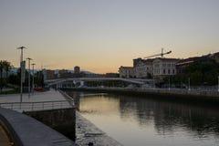 Solnedgång i riaen del Nervion framme av det Guggenheim Bilbao museet Arkivbilder