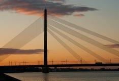 Solnedgång i Riga, kabel-bliven bro royaltyfri fotografi