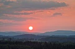 Solnedgång i rosa färger över de skogsbevuxna bergen Royaltyfri Fotografi