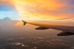 Solnedgång i skymningtid med vingen av en flygplan- och molnhimmel Foto som appliceras till turismoperatörer Royaltyfria Bilder