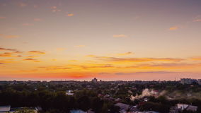 Solnedgång i staden Solen ställer in över horisonten, ljusen av husen tänds upp Dag till natttimelapse stock video