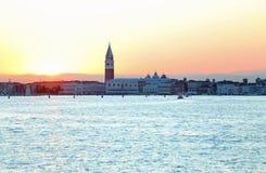 SOLNEDGÅNG i VENEDIG i Italien och campanilen av St Mark Arkivfoton