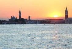 SOLNEDGÅNG i VENEDIG i Italien och campanilen av St Mark Arkivbild